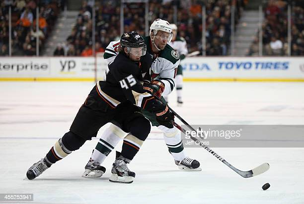 Sami Vatanen of the Anaheim Ducks and Dany Heatley of the Minnesota Wild fight for the puck in the second period at Honda Center on December 11, 2013...
