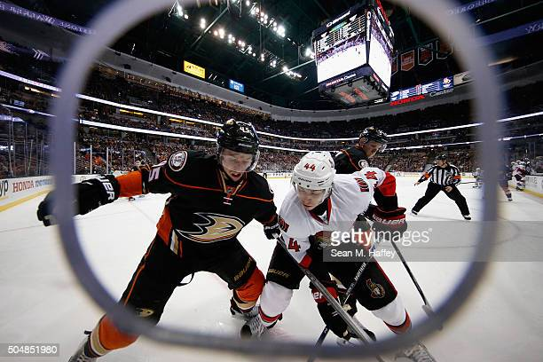 Sami Vatanen of the Anaheim Ducks battles JeanGabriel Pageau of the Ottawa Senators for a loose puck during the second period of a game at Honda...