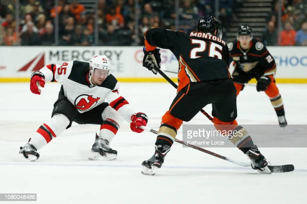 Sami Vatanen of the New Jersey Devils and Brandon Montour of the Anaheim Ducks fight for control of the puck at Honda Center on December 09 2018 in...