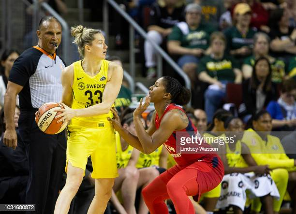 Sami Whitcomb of the Seattle Storm looks for an open teammate against the defense of Tierra RuffinPratt of the Washington Mystics during the first...
