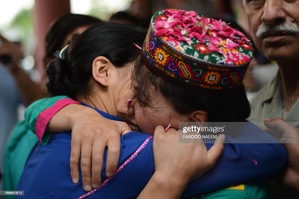 Samina Baig, (R) the first Pakistani woman climber to summit the world's highest peak Mount Everest, hugs a supporter on her arrival at Banezir airport in Islamabad on June 3, 2013. The 22-year-old Baig, from the small town of Shimshal in the Hunza valley in Pakistan's mountainous north, scaled the 8,848 metre (29,029 feet) peak early on 19 May after a gruelling expedition in rough weather. AFP PHOTO/Farooq NAEEM