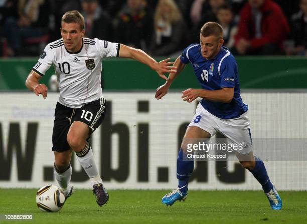 Samir Abbasov of Azerbaijan challenges Lukas Podolski of Germany during the EURO 2012 Group A Qualifier match between Germany and Azerbaijan at...