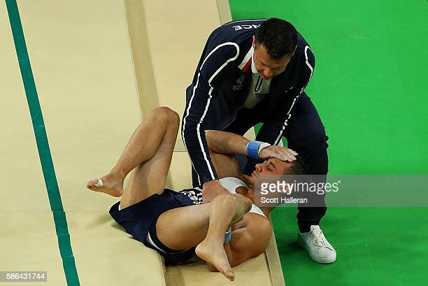 Samir Ait Said of France receives attention after breaking his leg while competing on the vault during the Artistic Gymnastics Men's Team...