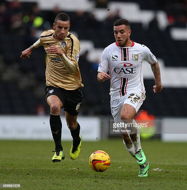 Samir Carruthers of Milton Keynes Dons moves forward with the ball away from Craig Eastmond of Colchester United during the Sky Bet League One match...