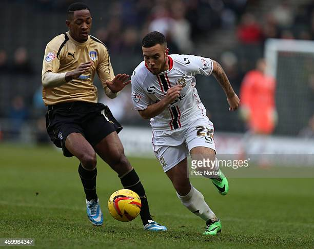 Samir Carruthers of Milton Keynes Dons moves forward with the ball away from Sanchez Watt of Colchester United during the Sky Bet League One match...