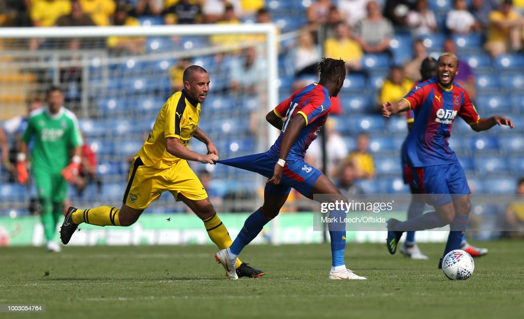 Samir Carruthers of Oxford pulls the shorts of Wilfried Zaha of Palace at Kassam Stadium on July 21, 2018 in Oxford, England.