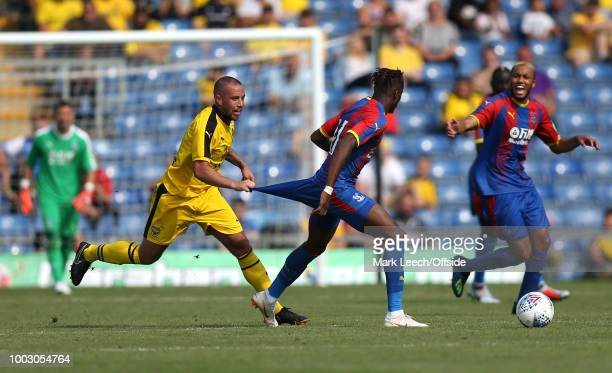 Samir Carruthers of Oxford pulls the shorts of Wilfried Zaha of Palace at Kassam Stadium on July 21 2018 in Oxford England