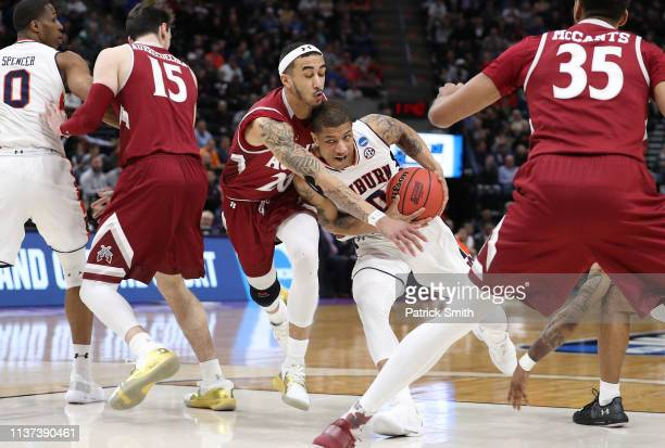 Samir Doughty of the Auburn Tigers drives to the basket against Trevelin Queen of the New Mexico State Aggies during the first half in the first...