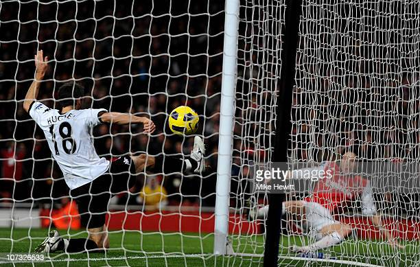 Samir Nasri of Arsenal scores the second goal past Aaron Hughes of Fulham during the Barclays Premier League match between Arsenal and Fulham at the...
