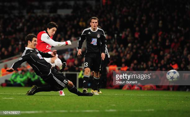 Samir Nasri of Arsenal shoots past Radosav Petrovic of FK Partizan Belgrade to score their third goal during theUEFA Champions League Group H match...