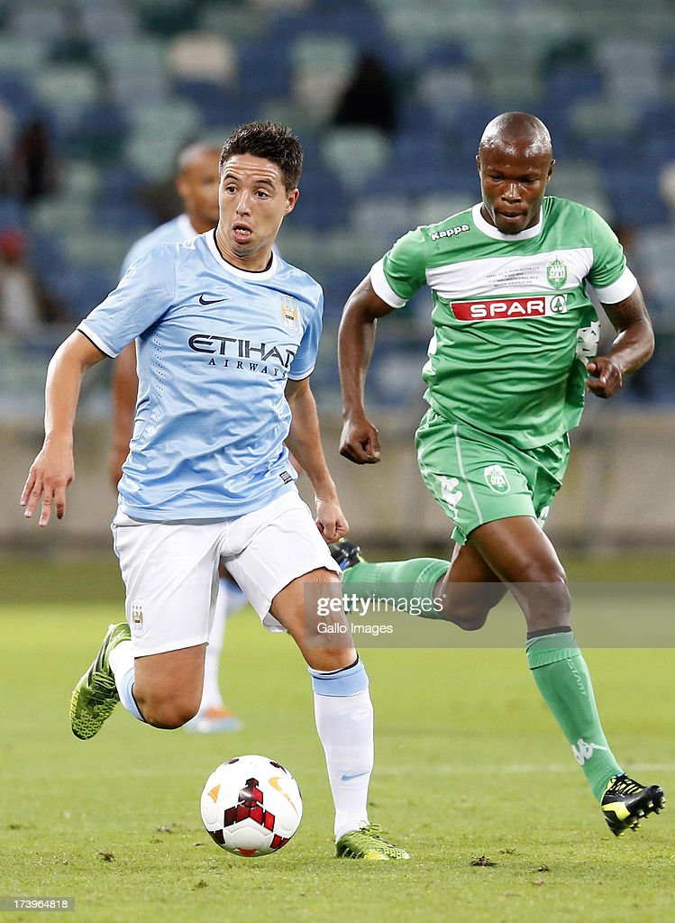 Samir Nasri of Manchester City bets Letladi Madubhanya during the Nelson Mandela Football Invitational match between AmaZulu and Manchester City at Moses Mabhida Stadium on July 18, 2013 in Durban, South Africa.