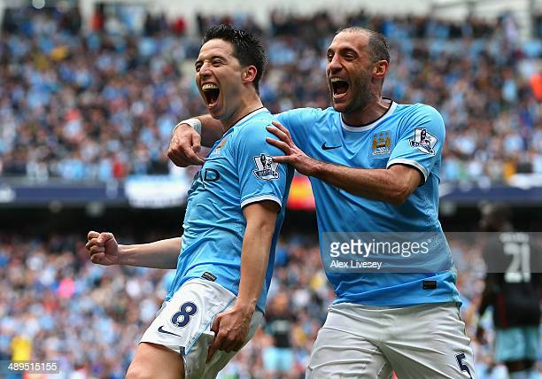 Samir Nasri of Manchester City celebrates scoring the first goal with teammate Pablo Zabaleta during the Barclays Premier League match between...
