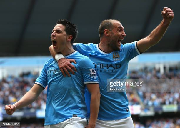 Samir Nasri of Manchester City celebrates scoring the first goal with team-mate Pablo Zabaleta during the Barclays Premier League match between...