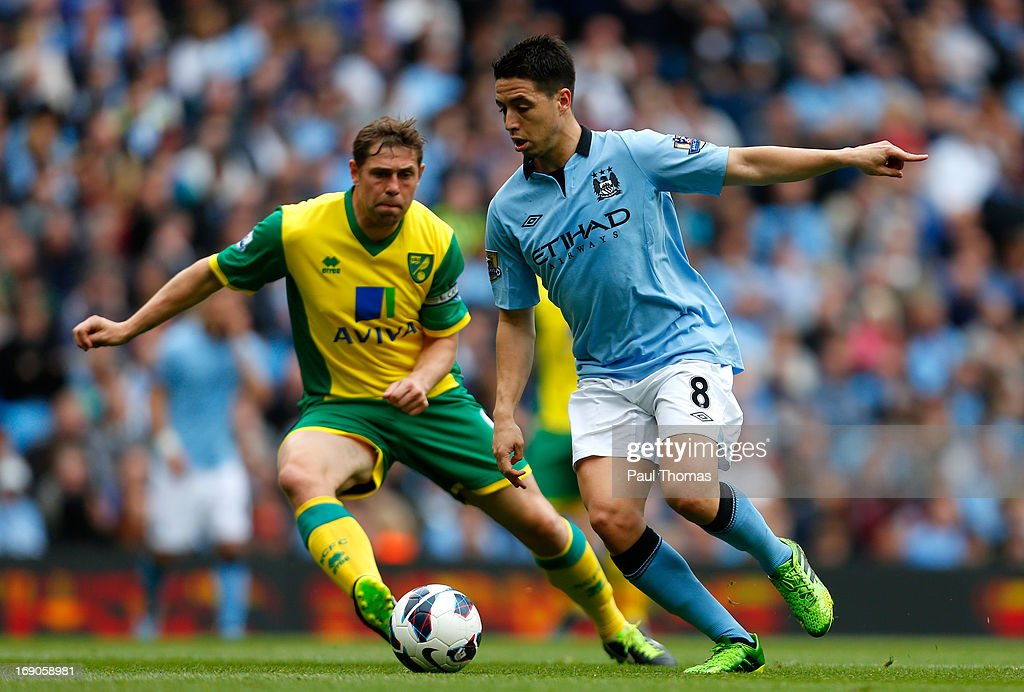 Samir Nasri (R) of Manchester City in action with Grant Holt of Norwich during the Barclays Premier League match between Manchester City and Norwich City at the Etihad Stadium on May 19, 2013 in Manchester, England.