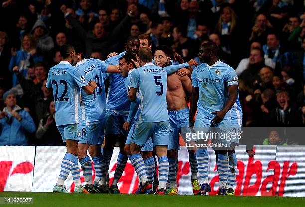 Samir Nasri of Manchester City is congratulated by teammates after scoring his team's second goal during the Barclays Premier League match between...