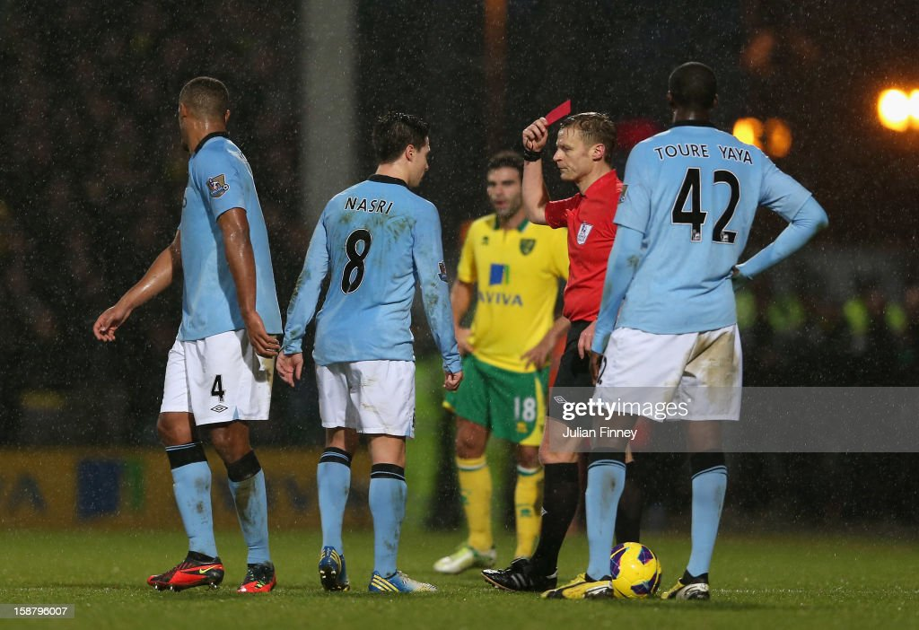 Samir Nasri of Manchester City is shown the red card by referee Mike Jones after he head butts Sebastien Bassong of Norwich City during the Barclays Premier League match between Norwich City and Manchester City at Carrow Road on December 29, 2012 in Norwich, England.