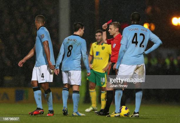 Samir Nasri of Manchester City is shown the red card by referee Mike Jones after he head butts Sebastien Bassong of Norwich City during the Barclays...