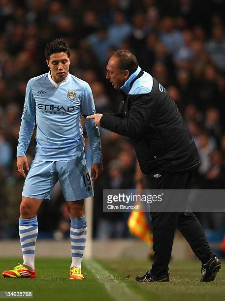 Samir Nasri of Manchester City is spoken to by David Platt assistant manager during the Barclays Premier League match between Manchester City and...