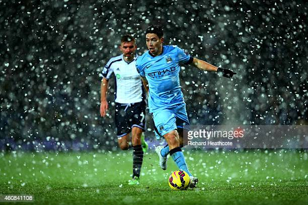 Samir Nasri of Manchester City runs with the ball as snow falls during the Barclays Premier League match between West Bromwich Albion and Manchester...