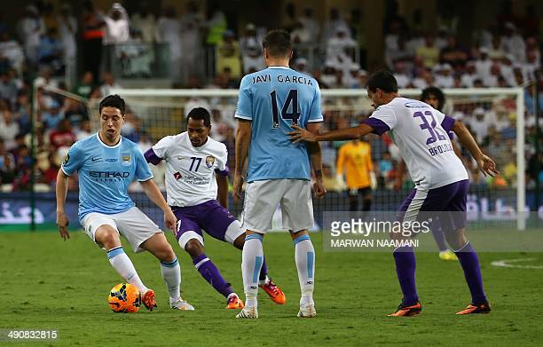 Samir Nasri of newlycrowned English Premier League champions Manchester City football team dribbles the ball between UAE's AlAin players Mohamed...