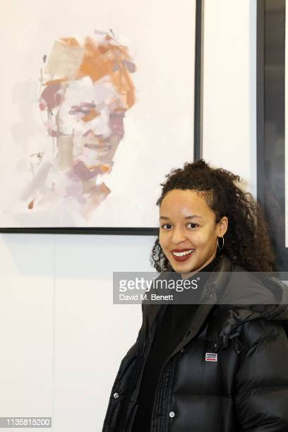 Samira Addo poses with her portrait from the Unmissable25 exhibition during the private view of The Other Art Fair at The Old Truman Brewery on March...