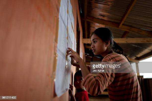 Samira Ali checks a posting on a wall of the social services office if they will receive food and supply ration inside the Sarimanok tent city on May...