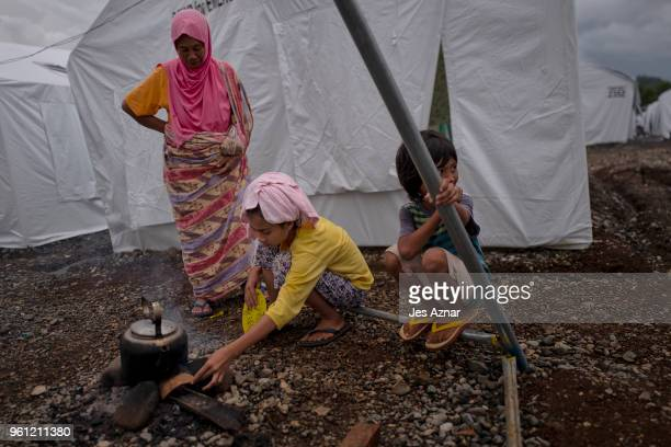 Samira Ali cook rice with her grandmother Kalili and sister Saira in front of their shelter inside the Sarimanok tent city on May 15 2018 in Marawi...