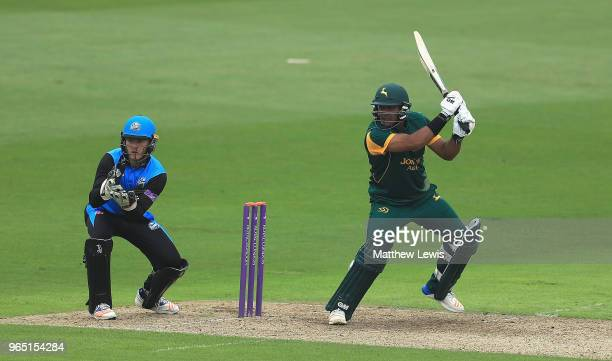 Samit Patel of Nottinghamshire hits the ball towards the boundary as Ben Cox of Worcestershire looks on during the Royal London OneDay Cup match...