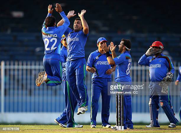 Samiullah Shenwari of Afghanistan is congratulated by Shafiqullah Shafiq after taking his fifth wicket of Irfan Karim of Kenya after he was caught by...