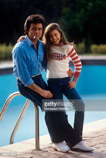 Sammarinese singer Little Tony with a cigarette in his mouth hugging his daughter Cristiana Ciacci sitting on a swimming pool ladder 1985