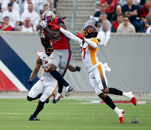 Sammie Coates of the Houston Roughnecks has the ball knocked loose by Harlan Miller of the LA Wildcats and Ahmad Dixon at TDECU Stadium on February...