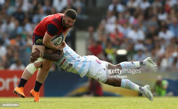 Sammy Arnold of Munster is tackled by Virimi Vakatawa during the European Rugby Champions Cup SemiFinal match between Racing 92 and Munster Rugby at...