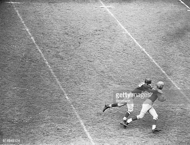 Sammy Baugh, of the Washington Redskins, vainly attempts to drag down John Weiss, of the New York Giants, who grabbed a pass from Marion Pugh, and...