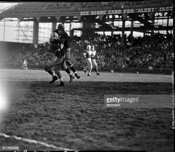 Sammy Baugh passing star of the Washington Redskins professional football team downs Eddie Rucinski of the Brooklyn Dodgers after the latter caught...
