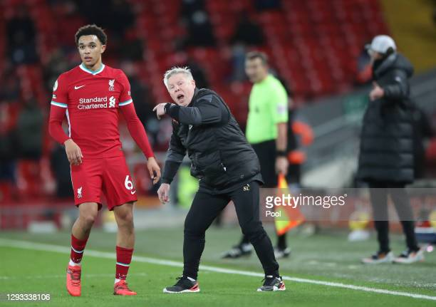 Sammy Lee, First Team Coach of West Bromwich Albion shouts instructions on the pitch as Trent Alexander-Arnold of Liverpool looks on during the...