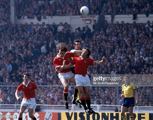 Sammy McIlroy and Lou Macari of Manchester United challenge for the ball with Liam Brady of Arsenal during the FA Cup Final held at Wembley Stadium...
