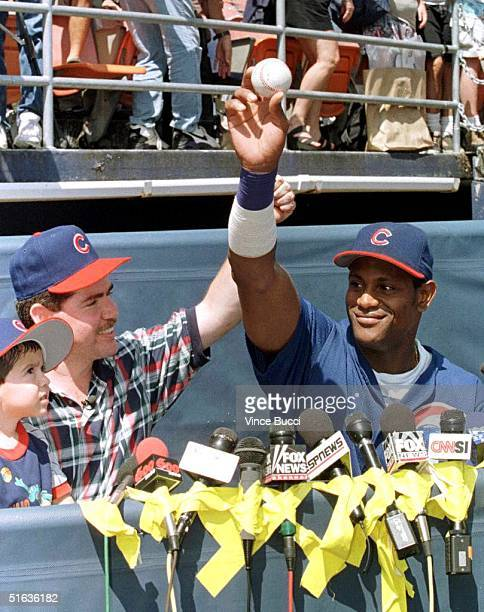 Sammy Sosa of the Chicago Cubs receives the ball he hit his 63rd homerun of the season with from Fabio Perez Mercado of Tijuana Mexico and his son...