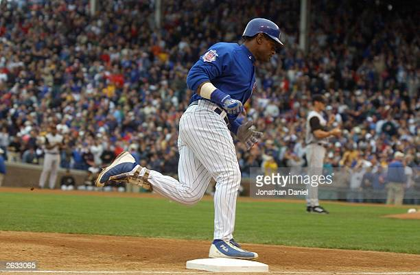 Sammy Sosa of the Chicago Cubs steps on third base as he trots to the plate after hitting a solo home run to center field against the Pittsburgh...