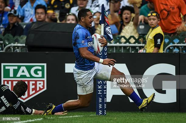 Samoa's Ed Fidow runs past New Zealand's Kurt Baker to score during their match on the second day of the Hong Kong Rugby Sevens tournament on April 9...