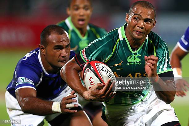 Samoa's Faalemiga Selesele tries to stop South Africa's Cornal Hendricks during an International Rugby Board Sevens World Series rugby union match in...