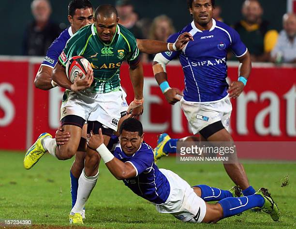 Samoa's Taulagi Afamasaga try to stop South Africa's Cornal Hendricks during an International Rugby Board Sevens World Series rugby union match in...