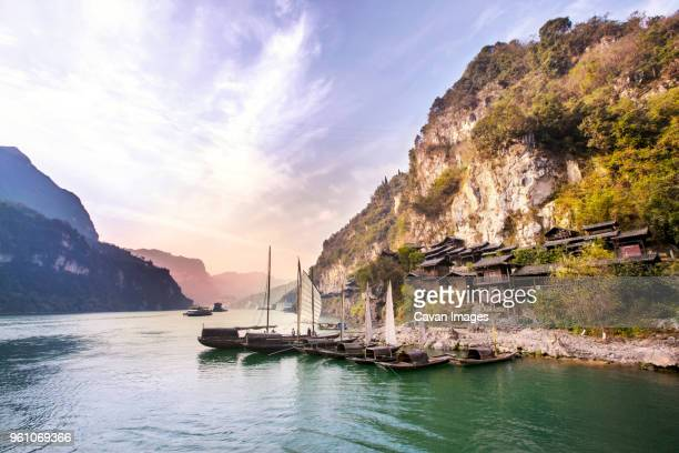 sampans moored in yangtze river by mountain against sky - yangtze river stock pictures, royalty-free photos & images