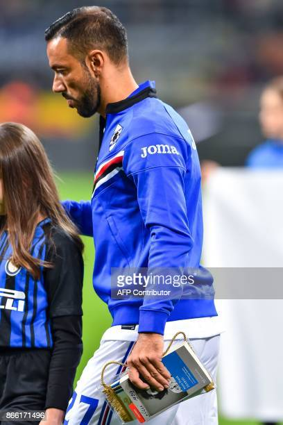 Sampdoria captain Fabio Quagliarella holds a copy of The Diary of Anne Frank before to give it to child mascot accompanying him onto the pitch at the...