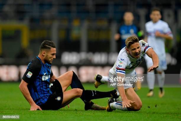 Sampdoria's Belgian midfielder Dennis Praet is tackled by Inter Milan's Italian defender Danilo D'Ambrosio during the Italian Serie A football match...
