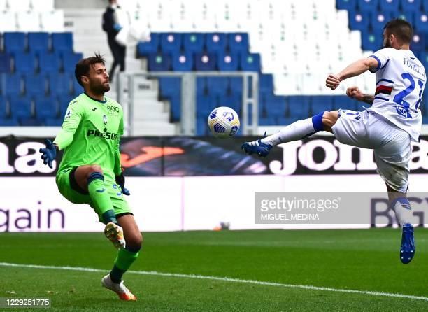 Sampdoria's Italian defender Lorenzo Tonelli fights for the ball with Atalanta's Italian goalkeeper Marco Sportiello during the Italian Serie A...