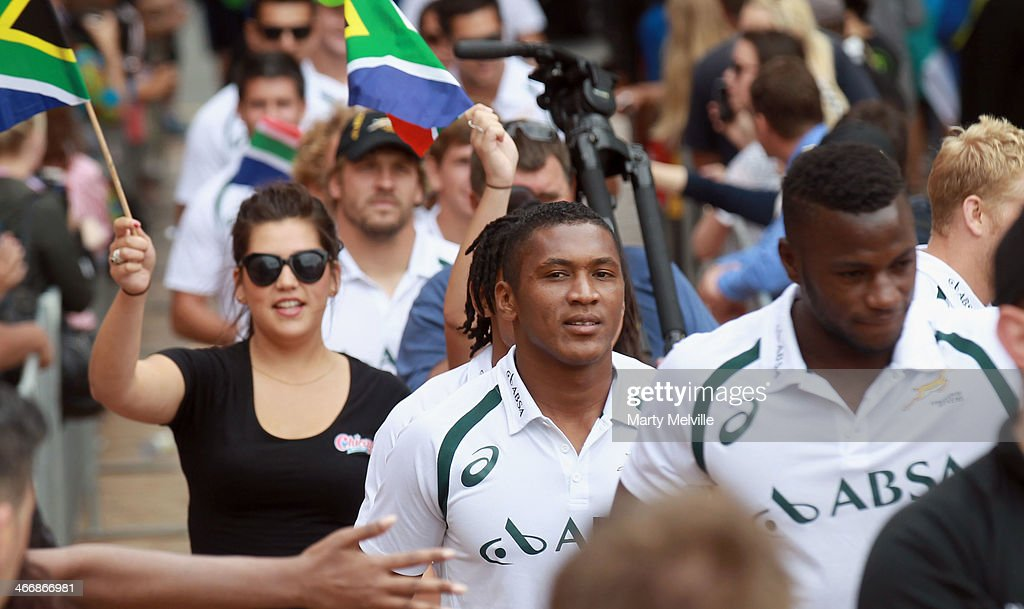 Sampie Mastriet (C) and Jamba Ulengo (R) walk through the crowds in Civic Square during a South African street parade ahead of the 2014 Wellington Sevens on February 5, 2014 in Wellington, New Zealand.