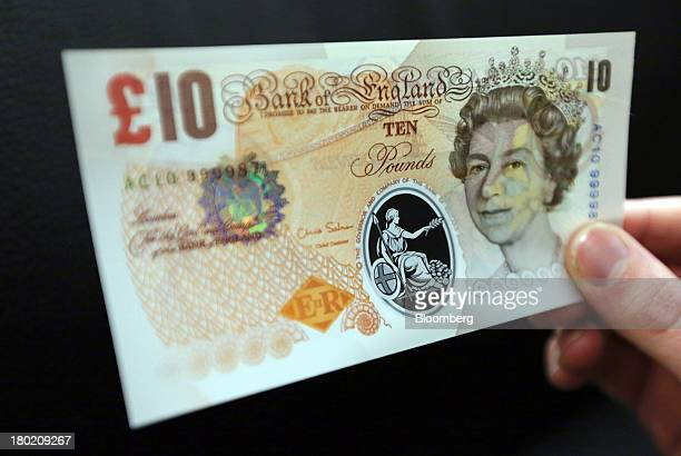 A sample Polymer ten pound British banknote is held for an arranged photograph during a news conference at the Bank of England in London UK on...