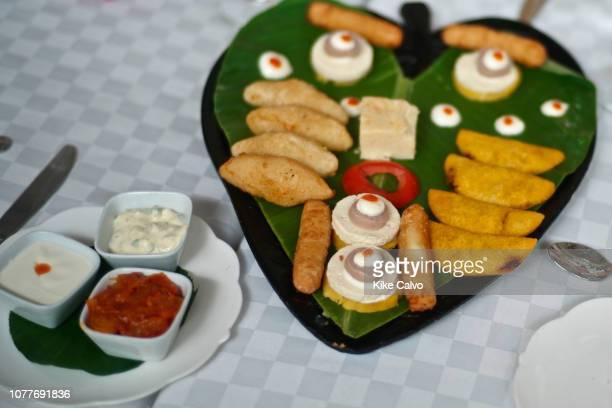 Sampling of Colombian food delicacies including carimanolas de jaiba empanaditas de carne deditos de queso bollo de mazorca butifarra queso costeno y...