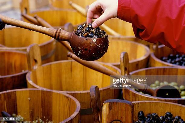 sampling olives at market - bancarella di verdura foto e immagini stock