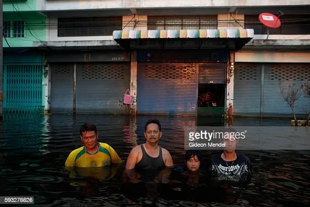 Samran Pannarat Wanchai Palagawong Tanee Yoo Suksawan and Tanicha Songbangjak pause to be photographed while walking through the chest high...